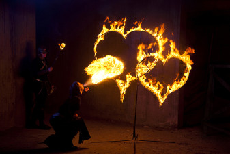 Woman Fire Performer setting fire to two flaming hearts